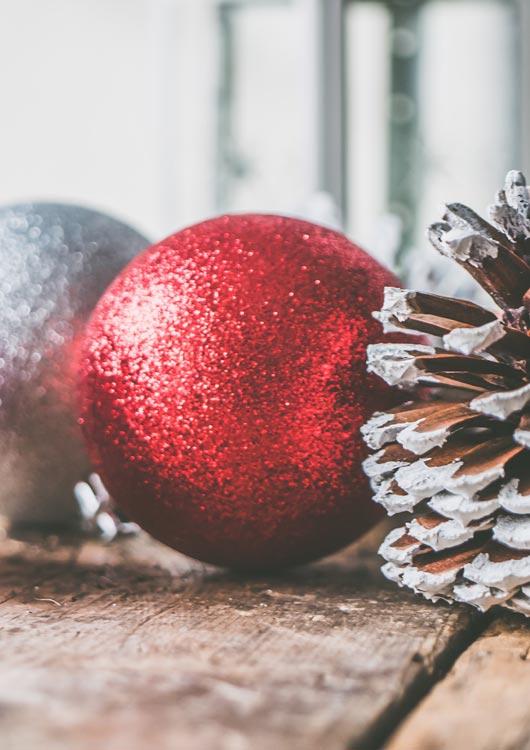 Vibes-Kachel zum Thema Christbaumschmuck mit einer roten und silbernen Weihnachtskugel sowie einem Tannenzapfen