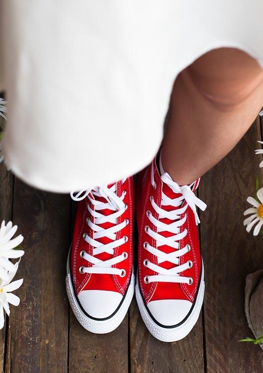Frau mit weißem Kleid steht mit roten Converse Sneakern auf dunklem Holzboden