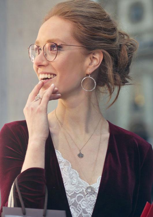 Junge Frau, die durch eine Brille nach links blickt und silberne Creolen trägt