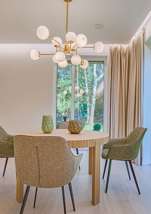 Helles Esszimmer mit rundem Holztisch, vier Stühlen und einer goldenen Deckenlampe