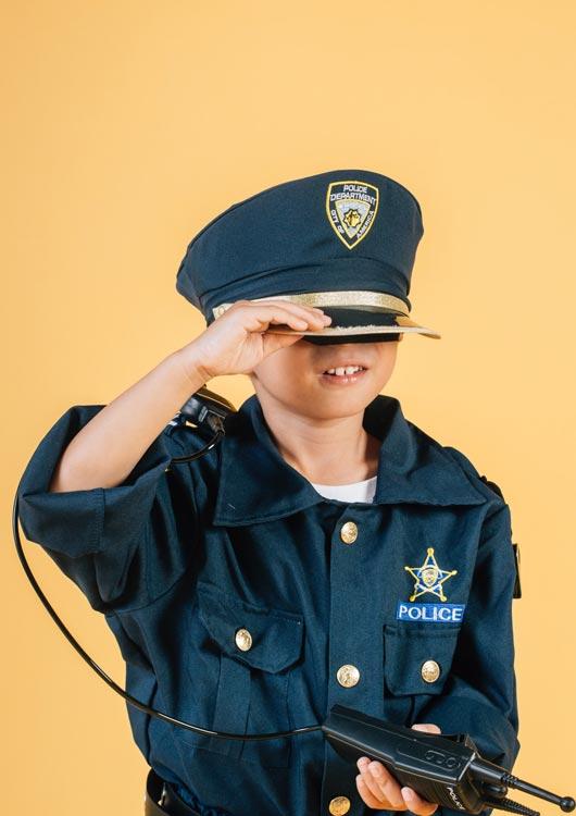 Vibes-Kachel zum Thema Fasching mit einem kleinen Jungen im Polizei-Kostüm vor hellorangenem Hintergrund