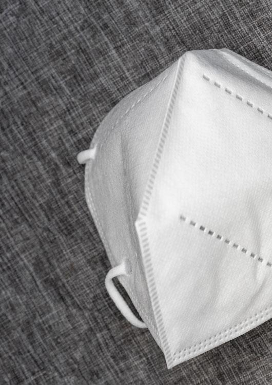 Vibes-Kachel zum Thema FFP2-Masken mit einer weißen Atemschutzmaske auf einem grauen Hintergrund liegend