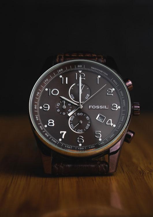 Vibes-Kachel zum Thema Uhren mit einem Chronographen mit schwarzem Ziffernblatt der Marke Fossil, welcher auf einem dunklen Holz