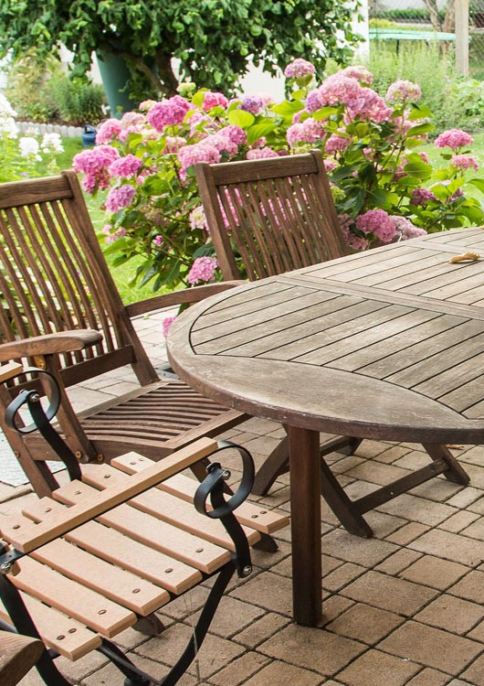 Gartengarnitur aus Holz auf einer Terrasse vor rosanen Blüten