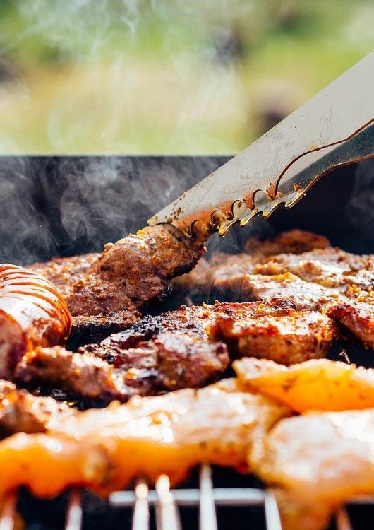 Fleisch, das mit einer Grillzange auf den Grill gewendet wird
