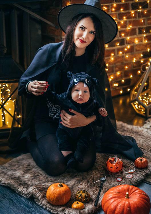 Vibes-Kachel zum Thema Halloween mit einer als Hexe verkleideten Frau, die ein als Monster verkleidetes Baby auf dem Schoß hält