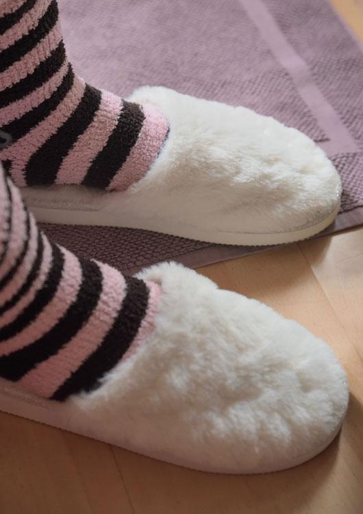 Person mit schwarz-rosa gestreiften Socken in weißen Plüsch-Hausschuhen