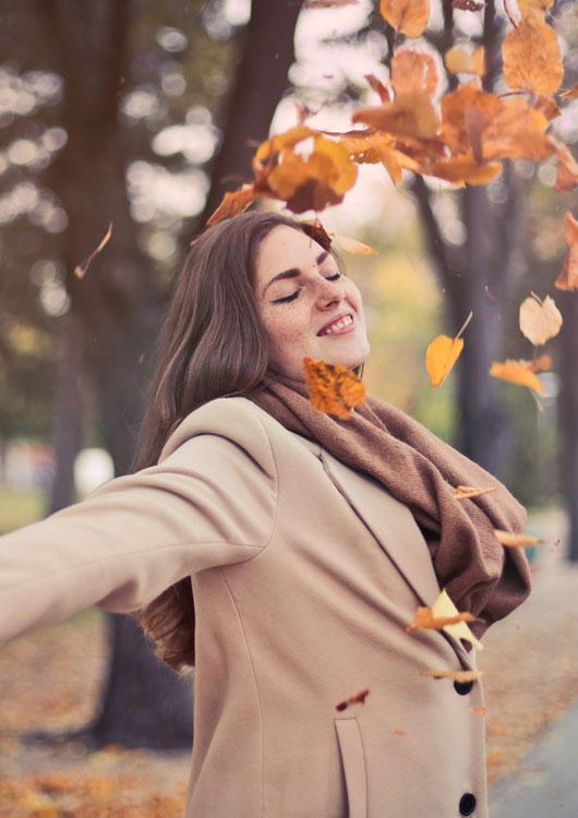 Frau im beige-farbenen Mantel schmeißt Herbstlaub in die Luft und grinst