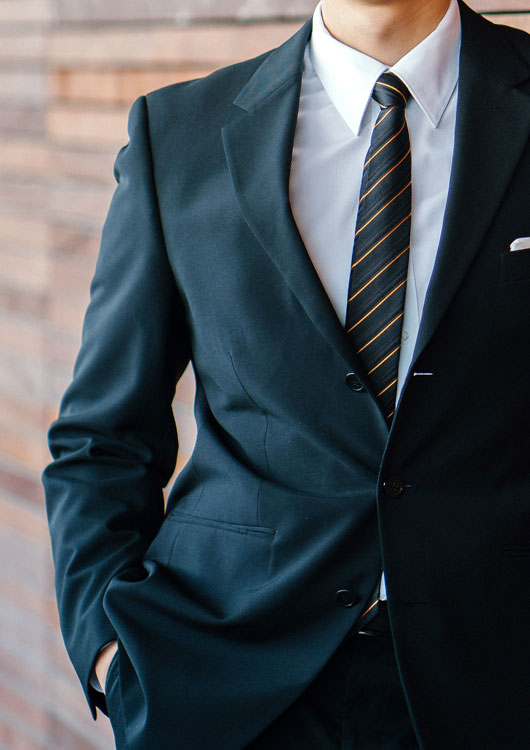 Vibes-Kachel zum Thema Herrenmode mit einem Mann in dunklem Anzug, der mit weißem Hemd und gestreifter Krawatte an eine Holzwand