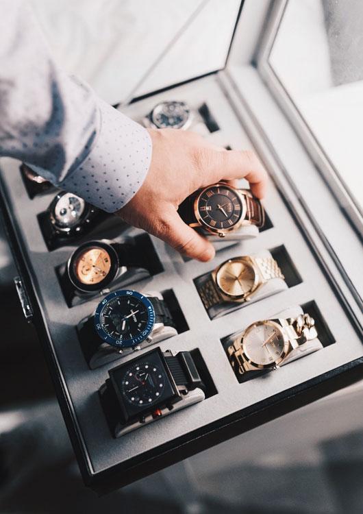 Hand holt eine Armbanduhr aus einem Uhrenkasten