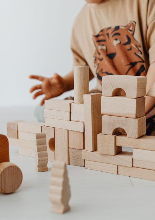 Kleinkind mit beige-farbenem Tiger-Shirt, welches mit Bauklötzen aus Holz spielt