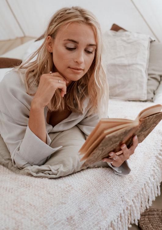 Vibes-Kachel zum Thema Hygge mit einer jungen Frau, die auf einer weißen Decke ein Buch liest