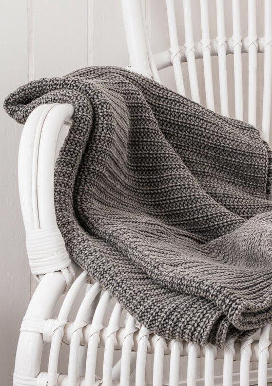 Vibes-Kachel zum Thema Wohnen mit einer grauen Kuscheldecke von IB Laursen, die auf einem weißen Stuhl liegt