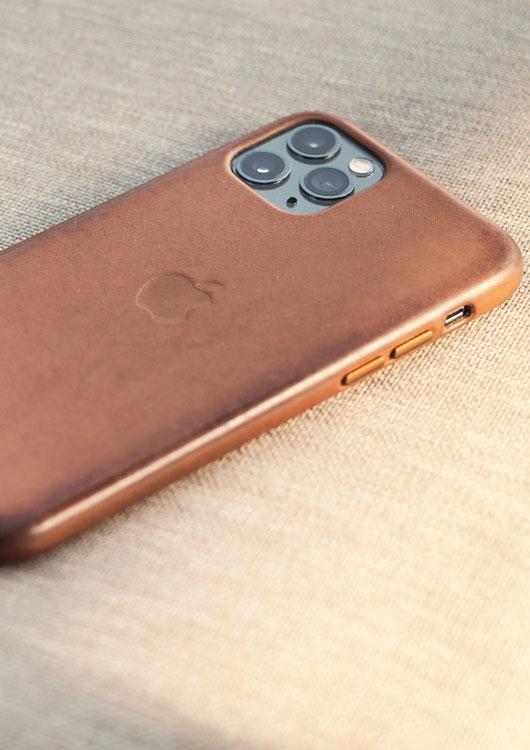 Vibes-Kachel zum Thema Handy mit einem iPhone 11 in einer hellbraunen Lederhülle