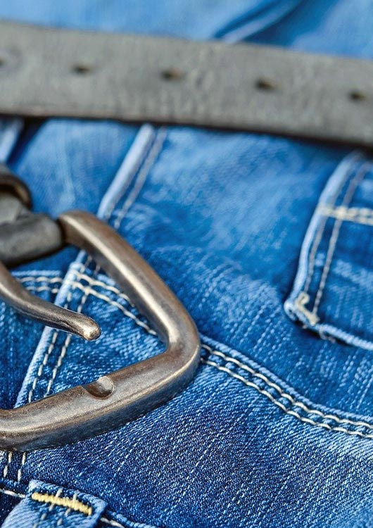 Vibes-Kachel zum Thema Jeans mit einer blauen Jeans auf der ein schwarzer Gürtel liegt