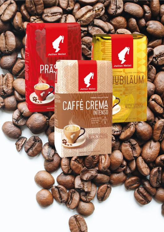 Drei unterschiedliche Kaffeesorten der Marke Julius Meinl mit Kaffeebohnen im Hintergrund