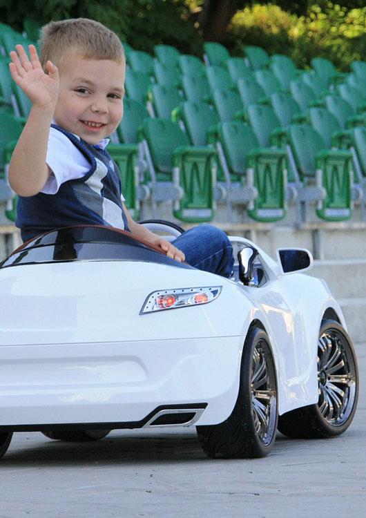 Kind winkt aus einem weißen Elektroauto zu