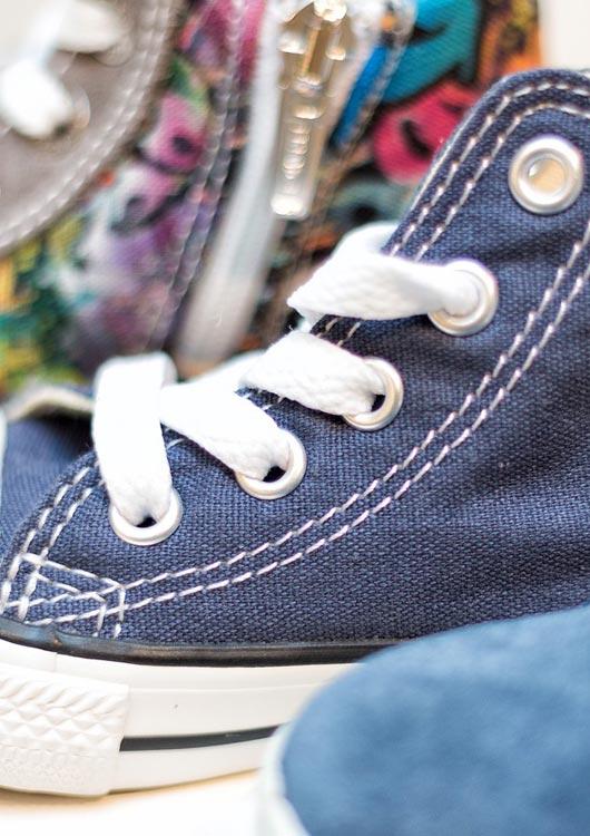 Vibes-Kachel zum Thema Kinderschuhe mit einem dunkelblauen Converse Sneaker für Kinder
