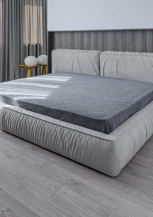 Vibes-Kachel zum Thema Matratzen mit einer großen, grauen Matratze auf einem weißen Doppelbett