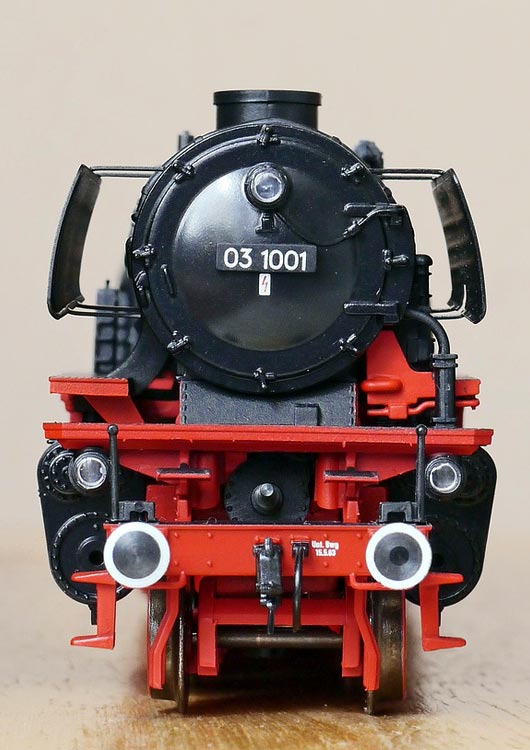Vibes-Kachel zum Thema Modellbahn mit einer schwarz-roten Dampflok als Modell auf einem Holztisch stehend