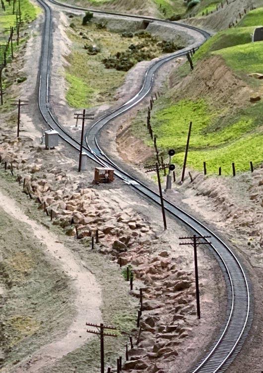 Vibes-Kachel zum Thema Modellbahn mit einer Gleisanlage in künstlicher Naturkulisse