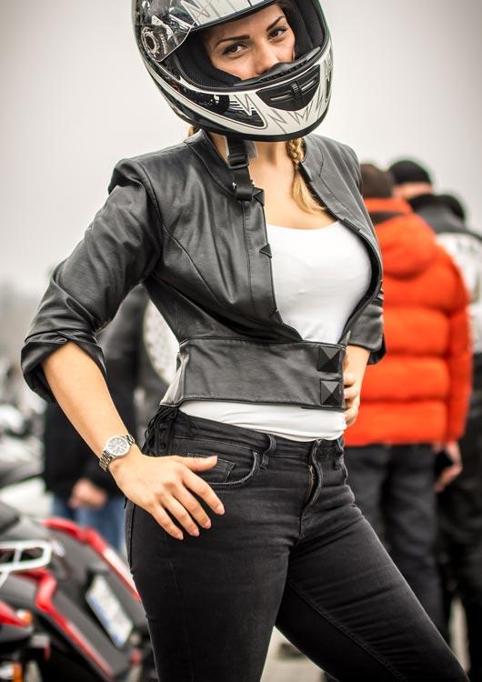 Junge Frau posiert in schwarzer Jeans, schwarzer Lederjacke und mit schwarz-weißem Helm auf dem Kopf