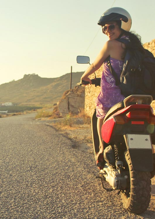 Vibes-Kachel zum Thema Motorroller mit einer jungen Frau im lila Kleid, die auf einem roten Scooter sitzt und zurückschaut