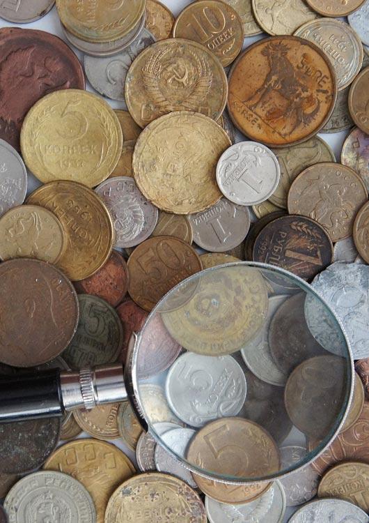 Vibes-Kachel zum Thema Sammeln & Seltenes mit einem Haufen unterschiedlicher Münzen und einer Lupe, die auf den Münzen liegt