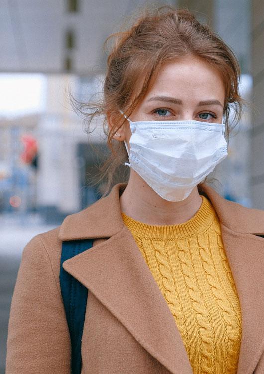 Vibes-Kachel zum Thema Corona-Krise mit einer jungen, rothaarigen Frau, die ein Mund-Nasen-Schutz trägt