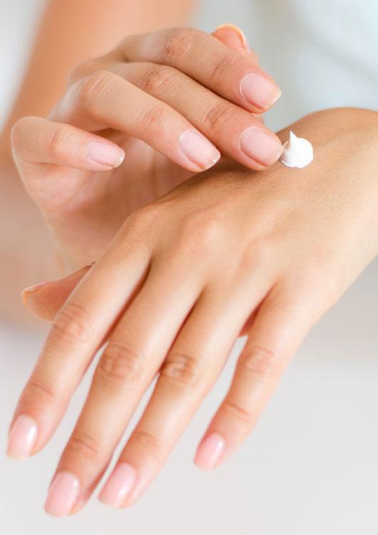 Vibes-Kachel zum Thema Naturkosmetik mit zarten weiblichen Händen, die Handcreme auf dem Handrücken verteilen