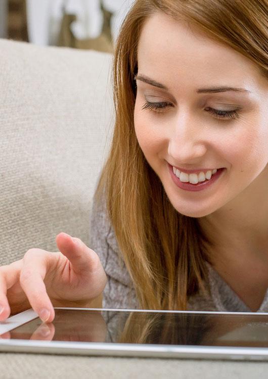 Einer junge Frau, die auf einer Couch liegt und lächelnd auf ihr Tablet schaut