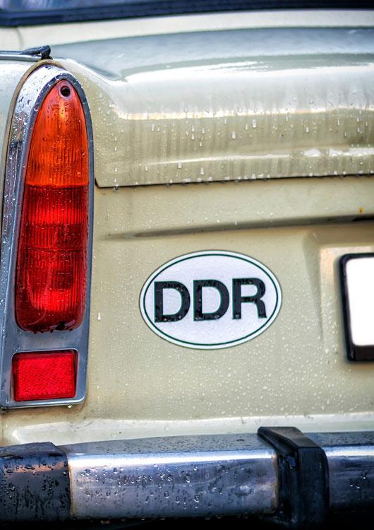 Heckansicht eines beige-farbenen Trabants mit DDR-Aufkleber