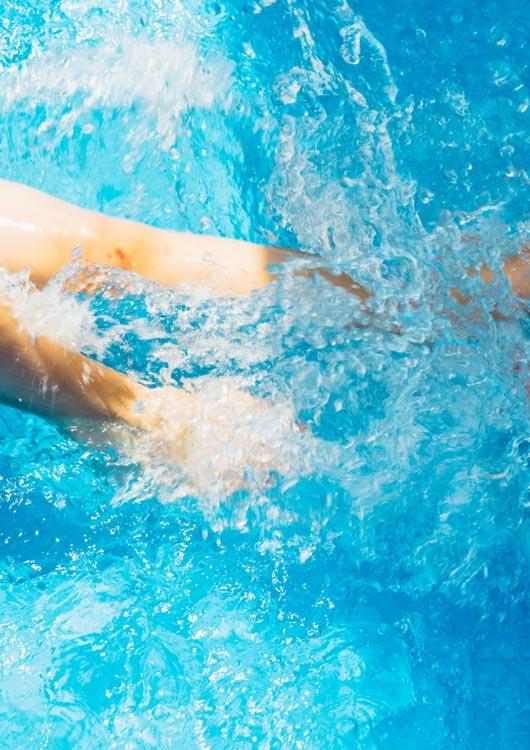 Vibes-Kachel zum Thema Pool mit im klarem, hellblauen Wasser planschenden Beinen