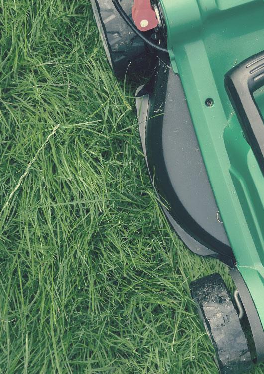 Vibes-Kachel zum Thema Rasenmäher mit einem grün-schwarzen Rasenmäher von oben betrachtet auf einem ungemähtem Rasen