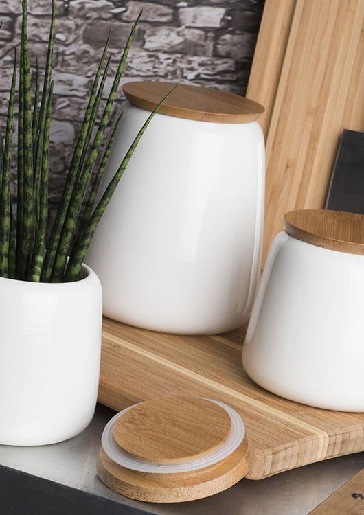 Vibes-Kachel zum Thema Dekoration mit einer weißen Vase, zwei weißen Vorratsbehältern und einem Schneidebrett aus Holz