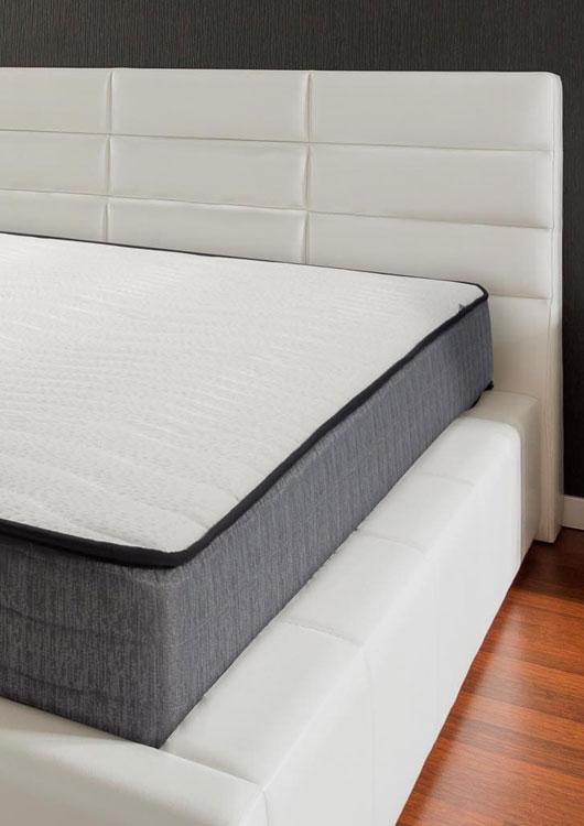Vibes-Kachel zum Thema Matratzen mit einem weißen Bett auf der eine grau-weiße Schaummatratze liegt