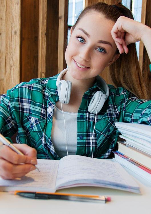 Schülerin im grünen Karohemd sitzt mit Kopfhörern an ihren Hausaufgaben und stützt ihren Kopf ab
