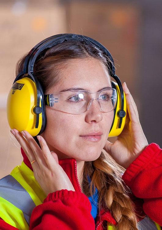 Junge Frau mit gelbem Gehörschutz, gelber Sicherheitsweste und Schutzbrille