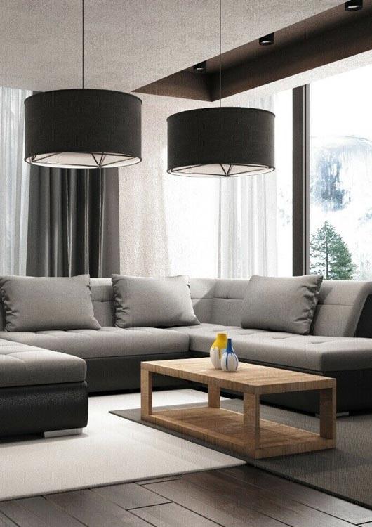 Graue Sofagarnitur in beleuchtetem Wohnzimmer mit Holztisch und zwei Hängelampen