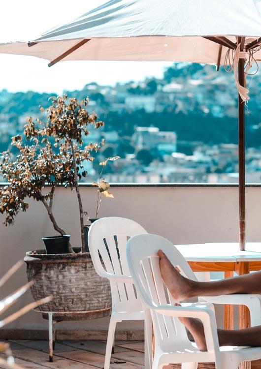 Vibes-Kachel zum Thema Sommer mit einem Sonnenschirm auf einem Balkon mit weißen Möbeln