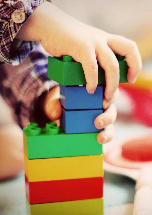 Kleinkind baut einen Turm aus Duplo Steinen