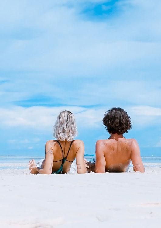 Vibes-Kachel zum Thema Urlaub mit einer schwarzen Sonnenbrille, die auf einem orangenen Strandtuch am Meer liegt