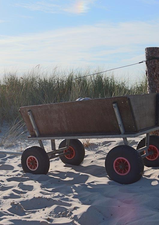 Vibes-Kachel zum Thema Vatertag mit einem Bollerwagen aus Holz, der im Sand steht