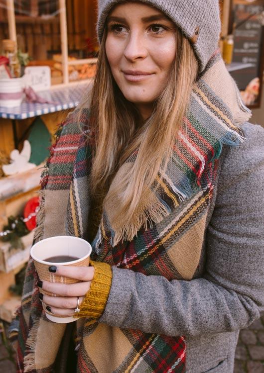 Vibes-Kachel zum Thema Weihnachtsmarkt mit einer jungen Frau, die warm eingepackt einen Glühwein in der Hand hält